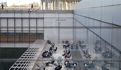 Image of students sitting on a balcony studying.