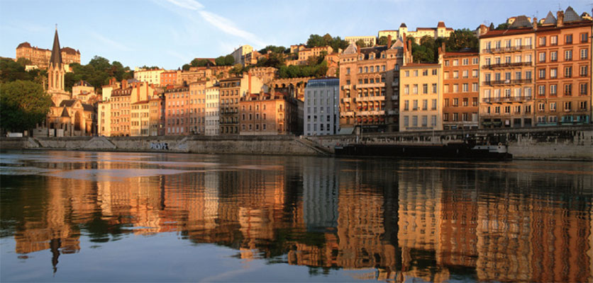 Image of the city of Lyon. One of the rivers is in the foreground and buildings are in the background.