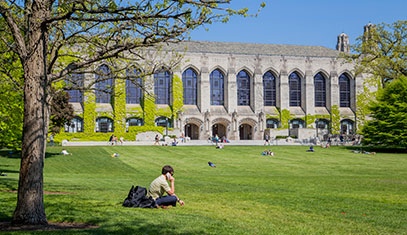 Image of a student sitting on the Northwestern lawn.