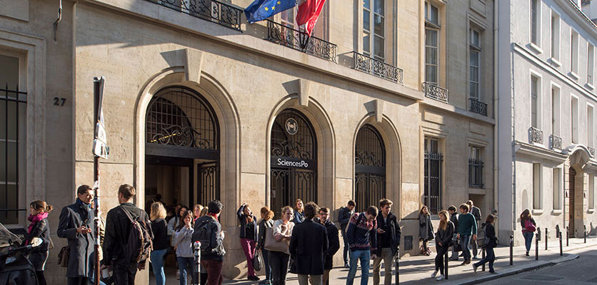 Image of students standing on the street outside a building on the Sciences Po campus.